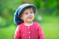 Baby girl wearing a big knitted hat in sunny garden Royalty Free Stock Photography