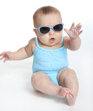 Baby girl wearing a blue swimsuit and sunglasses. Isolated on the white background royalty free stock photography
