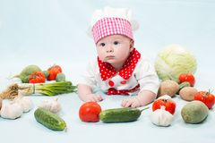 Baby girl  wearing a chef hat with vegetables Stock Image