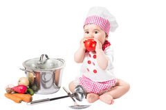 Baby girl  wearing a chef hat with vegetables and pan. Royalty Free Stock Images