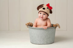 Baby Girl Wearing a Crocheted Puppy Dog Hat. Six Month Old Baby Girl Wearing a Crocheted Puppy Dog Hat. Shot in the Studio on a White Wooden Floor and Backdrop royalty free stock photo