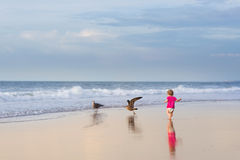 Baby girl wearing diaper and pink shirt running on beach Royalty Free Stock Photos