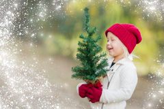 Baby Girl Wearing Mittens Holding Small Christmas Tree with Snow Effe Stock Photos