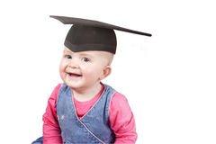 Baby girl wearing a mortar board hat. Young girl age 1 wearing a school graduation mrtar board hat Royalty Free Stock Image