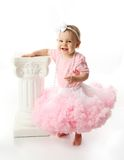 Baby girl wearing pettiskirt tutu. Portrait of a sweet infant wearing a pink tutu, necklace, and headband bow, isolated on white in studio Stock Photography
