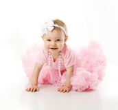 Baby girl wearing pettiskirt tutu crawling. Portrait of a sweet infant wearing a pink tutu, necklace, and headband bow, isolated on white in studio Stock Images
