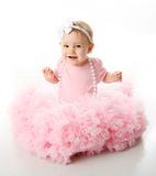 Baby girl wearing pettiskirt tutu and pearls. Portrait of a sweet infant wearing a pink tutu, necklace, and headband bow, isolated on white in studio Royalty Free Stock Images