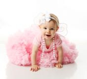 Baby girl wearing pettiskirt tutu and pearls. Portrait of a sweet infant wearing a pink tutu, necklace, and headband bow, isolated on white in studio Royalty Free Stock Photos