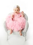 Baby girl wearing pettiskirt tutu and pearls. Portrait of a sweet infant wearing a pink tutu, necklace, and headband bow, isolated on white in studio sitting in Stock Photography