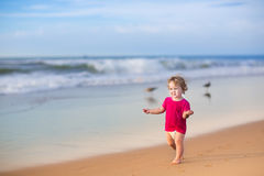 Baby girl wearing pink shirt and diaper on beach. Beautiful baby girl with curly hair wearing a pink shirt and a diaper on beach Stock Photo