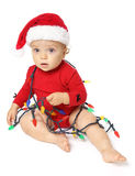 Baby girl wearing a Santa Claus hat, playing with Christmas lighting equipment Stock Images