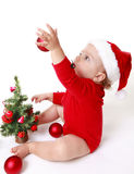 Baby girl wearing a Santa Claus hat, playing with red balls, near the Christmas Tree Stock Image