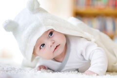 Baby girl wearing white towel or winter overal in white sunny bedroom. Baby girl with blue eyes wearing white towel or winter overal in white sunny bedroom Royalty Free Stock Photo