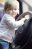 Baby girl at the wheel. Beautiful baby girl driving a big car stock photo