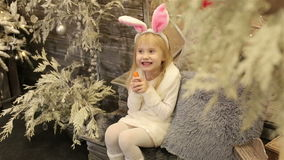 Baby girl in white costume of rabbit sits among christmas decorations and eats a carrot. Happy small girl celebrates Christmas and New year in fur suit of stock video