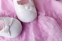 Baby girl white dancing shoes near leotards Royalty Free Stock Images