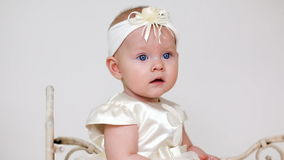 Baby girl in white dress and headband sitting stock video footage