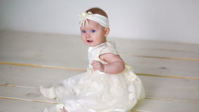 Baby girl in white dress and headband sitting stock footage