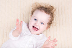 Baby girl in a white dress on knitted blanket Royalty Free Stock Images