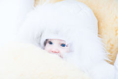 Baby girl in a white fur jacket sitting in a stroller with a warm sheepskin foot muff Stock Photo