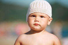Baby girl in white hat on the beach Stock Images