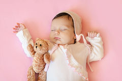 Baby girl in white hat and pink pajamas hugging teddy bear sleeps in his bloodstream on a  blanket Royalty Free Stock Photography