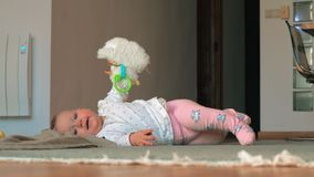 A baby girl in pink tights lying on a floor with toy sheep stock video
