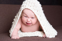 Baby girl in white woolen scarf crying Stock Image