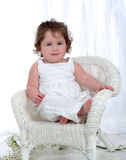 Baby Girl on Wicker Chair. Baby girl sitting on wicker chair in front of white background with flowers on floor Royalty Free Stock Image