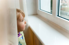 Baby girl at window. Baby girl standing at a window and looking out stock images