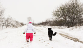 Baby girl in wintertime. Baby girl and her dog on the road with snow Royalty Free Stock Photos