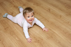 Baby girl on wooden floor. Overhead of baby girl on wooden laminate floor with copy space Stock Photo