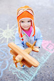 Baby girl with wooden toy airplane on a background of children's royalty free stock images
