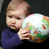 Baby girl with world globe. Portrait of cute baby girl or toddler holding colorful globe of world royalty free stock photo