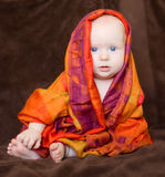 Baby girl wrapped in an orange scarf Royalty Free Stock Images