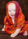 Baby girl wrapped in an orange scarf Stock Image