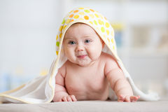 Baby girl wrapped towel in children nursery room. Newborn kid relaxing in bed after bath or shower. Royalty Free Stock Photos