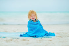 Baby girl wrapped in towel sitting on beach Stock Images