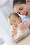 Baby girl wth her mother eating lunch. Baby girl eating lunch with help of her mommy royalty free stock image