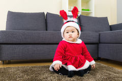 Baby girl with x mas dressing and seating on carpet Stock Photography