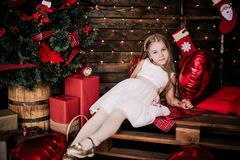 Baby girl 4-5 year old posing in room over christmas tree with decorations. Looking at camera. Merry christmas. Wearing stylish dr Stock Photography
