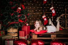 Baby girl 4-5 year old posing in room over christmas tree with decorations. Looking at camera. Merry christmas. Wearing stylish dr Royalty Free Stock Photo