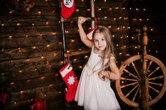 Baby girl 4-5 year old posing in room over christmas tree with decorations. Looking at camera. Merry christmas. Wearing stylish dr Royalty Free Stock Images