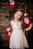 Baby girl 4-5 year old posing in room over christmas tree with decorations. Looking at camera. Merry christmas. Wearing stylish dr Royalty Free Stock Photography