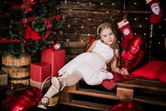 Baby girl 4-5 year old posing in room over christmas tree with decorations. Looking at camera. Merry christmas. Wearing stylish dr Stock Photo