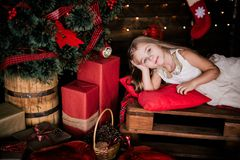 Baby girl 4-5 year old posing in room over christmas tree with decorations. Looking at camera. Merry christmas. Wearing stylish dr Stock Images