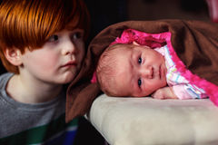 Baby Girl. 4 year old redhead boy cuddling with his new baby cousin -- image taken indoors using natural light Royalty Free Stock Images