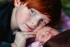 Baby Girl. 4 year old redhead boy cuddling with his new baby cousin -- image taken indoors using natural light Royalty Free Stock Photo