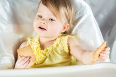 Baby girl in a yellow dress holding a cookie. In each hand royalty free stock photography