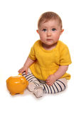 Baby girl with a yellow piggy bank. Cutout Stock Images